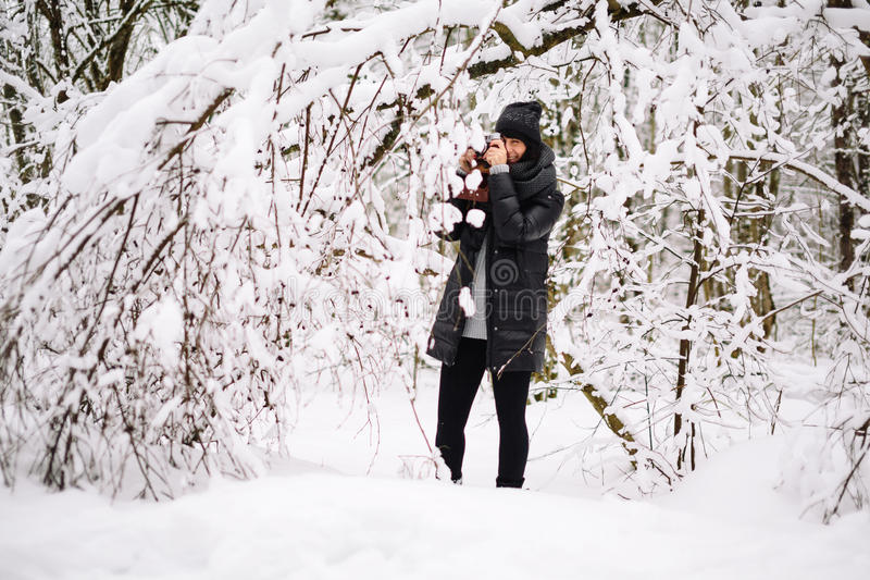Meisje in sneeuwbos wordt gefotografeerd dat stock fotografie
