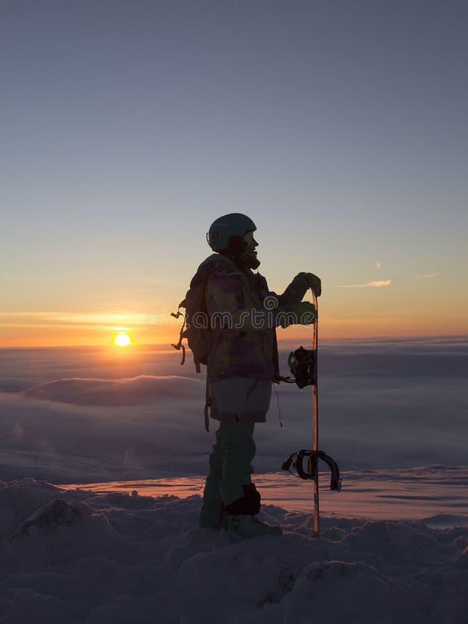 Meisje snowboarder op de berg bij dageraad stock afbeelding