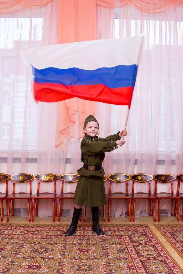 Meisje in Sovjet militaire eenvormige golvende vlag royalty-vrije stock fotografie