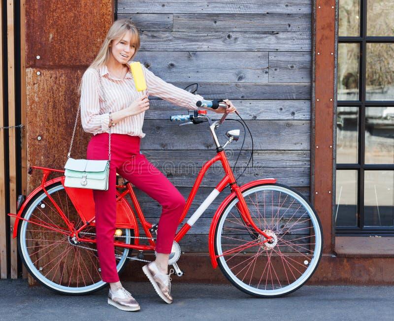 Meisje, stijl, vrije tijd en levensstijl - gelukkige jonge hipstervrouw die met handtas en rode uitstekende fiets roomijs op stad royalty-vrije stock foto