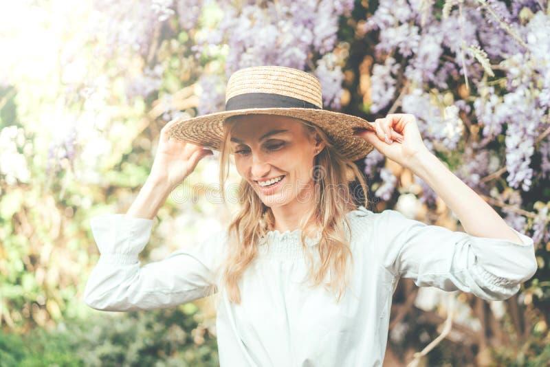 Meisje in strohoed en wisteria stock foto