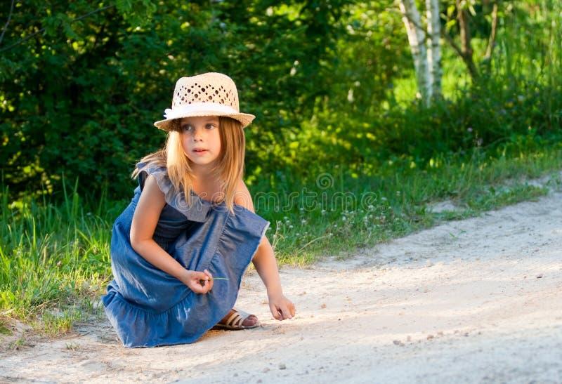 Meisje in strohoed het spelen. royalty-vrije stock fotografie