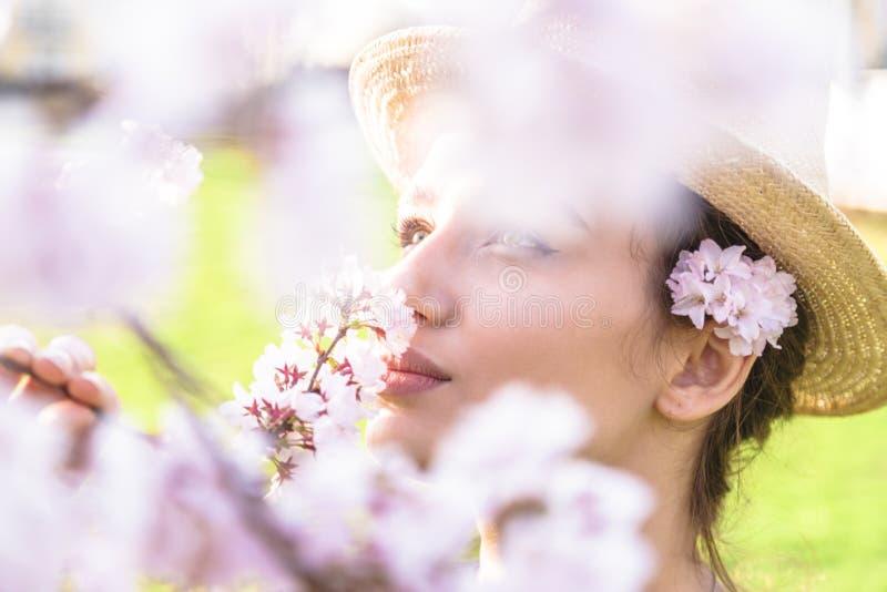 Meisje in strohoed met bloemen achter oor openlucht stock foto