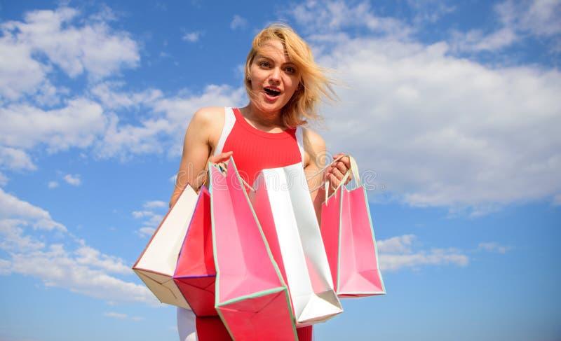 Meisje tevreden met aankopen Draagt de vrouwen rode kleding bos het winkelen achtergrond van de zakken de blauwe hemel Het winkel royalty-vrije stock afbeelding