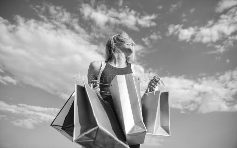 Meisje tevreden met aankopen Draagt de vrouwen rode kleding bos het winkelen achtergrond van de zakken de blauwe hemel Vind vrij  stock foto's