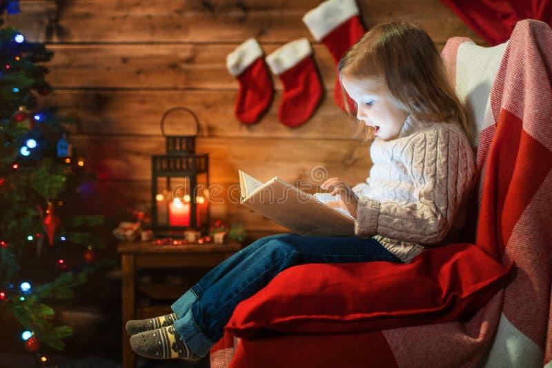 Meisje thuis met een Kerstmisboom, giften die een boekzitting lezen royalty-vrije stock foto's