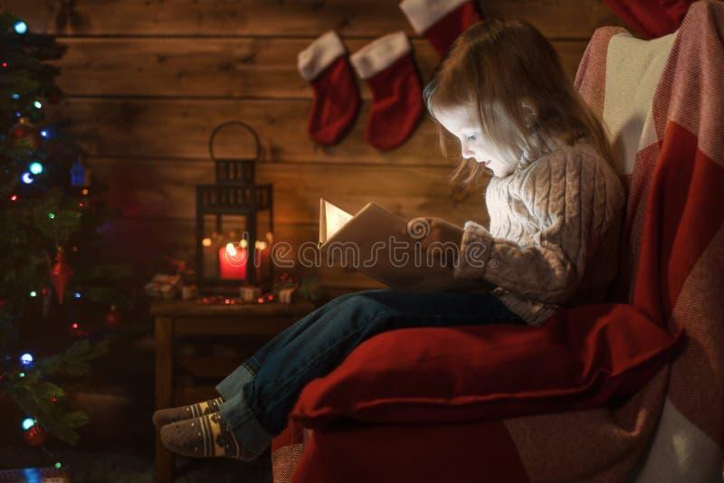 Meisje thuis met een Kerstmisboom, giften die een boekzitting lezen royalty-vrije stock afbeelding