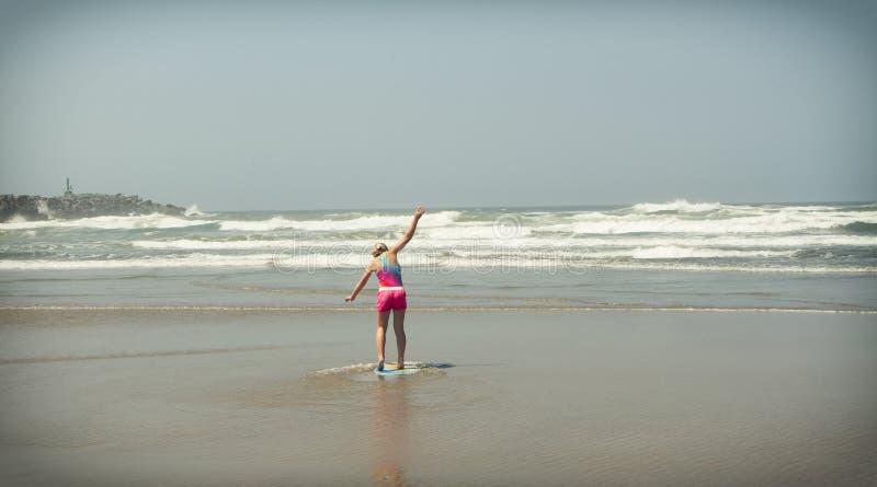 Meisje of tiener die een skimboard op de kust van Oregon leren te berijden royalty-vrije stock foto's