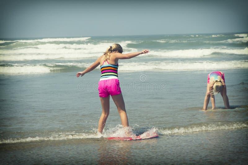 Meisje of tiener die een skimboard op de kust van Oregon leren te berijden stock foto
