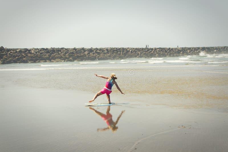 Meisje of tiener die een skimboard op de kust van Oregon leren te berijden royalty-vrije stock foto