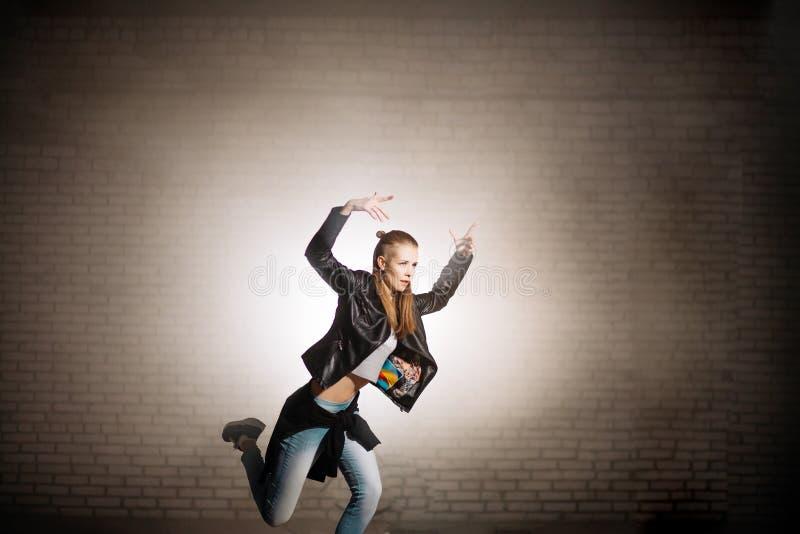 Meisje in toevallige clothers en zwart jasje op de taille runnig met opgeheven wapens royalty-vrije stock foto