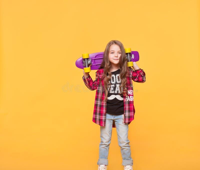 Meisje in toevallige die hipsterkleren over gele achtergrond wordt geïsoleerd stock afbeeldingen