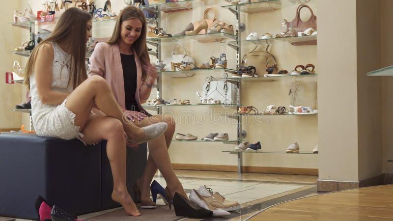 Meisje tryes op pantoffels bij de winkel stock foto