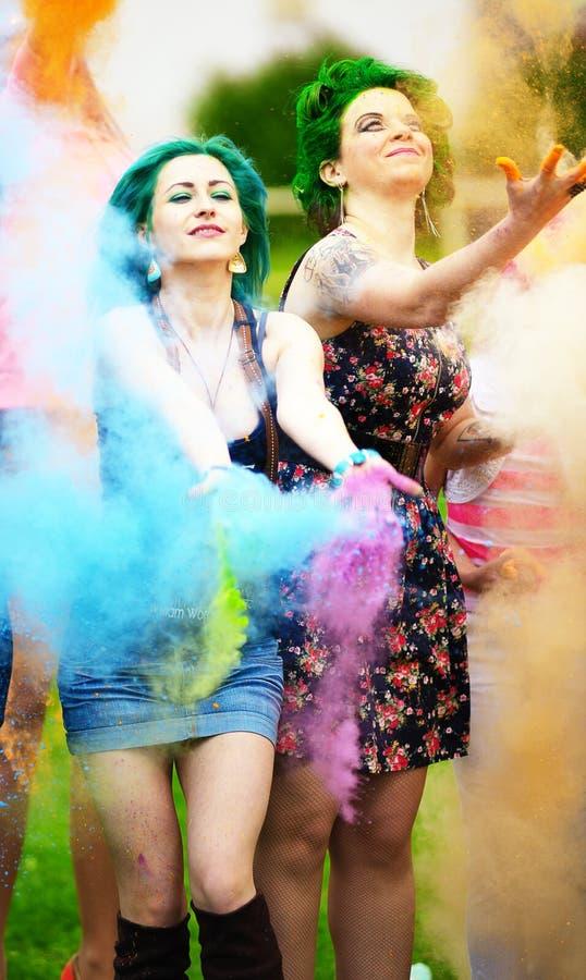 Meisje twee tijdens Holi-festival werpt kleurenverven stock foto's