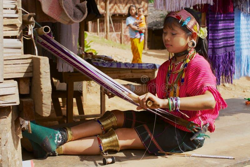 Meisje van de de heuvelstam die van Lahwi Padaung traditionele kledingsweefsels buiten een huis in Kayan-dorp, Thailand dragen stock afbeelding