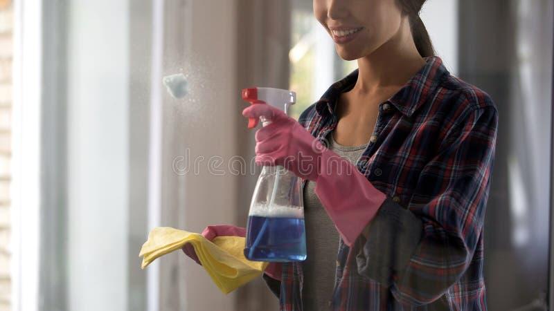 Meisje van de schoonmakende dienst die reinigende agenten toepassen op stoffige glasoppervlakten stock afbeelding