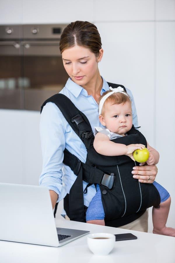 Meisje van de vrouwen het dragende baby terwijl het werken in laptop royalty-vrije stock afbeelding