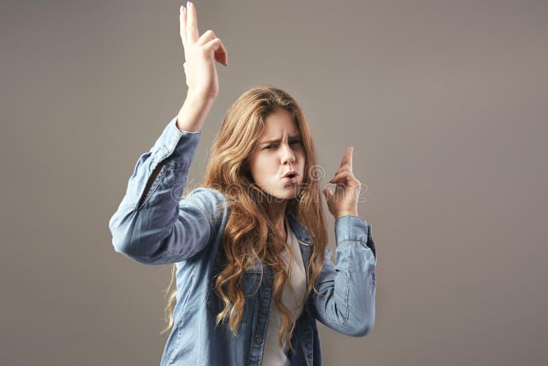 Meisje van Nice met lang bruin haar kleedde zich in een witte t-shirt, jeans en van het jeansoverhemd dwazen rond op een grijze a royalty-vrije stock afbeelding