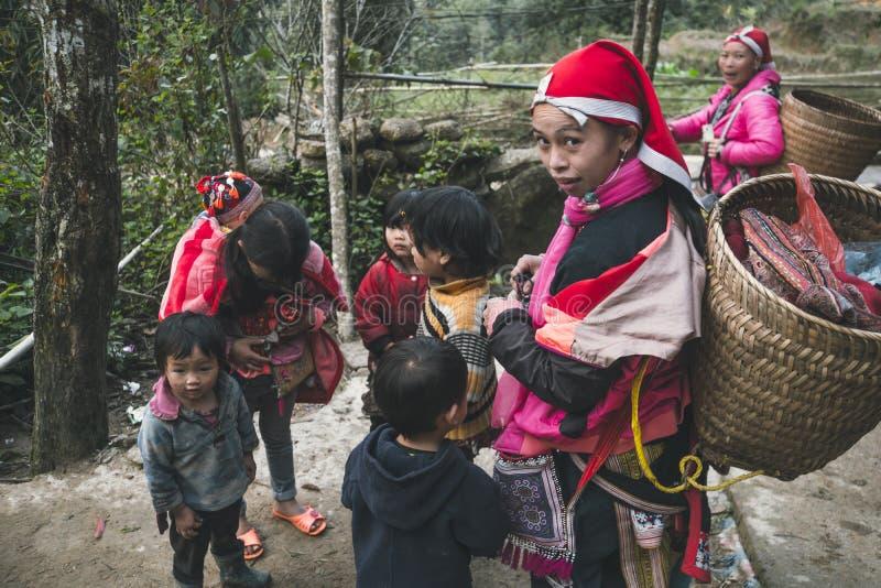 meisje van stam rode dzao, met een grote rieten die erachter mand, door kinderen wordt omringd royalty-vrije stock fotografie