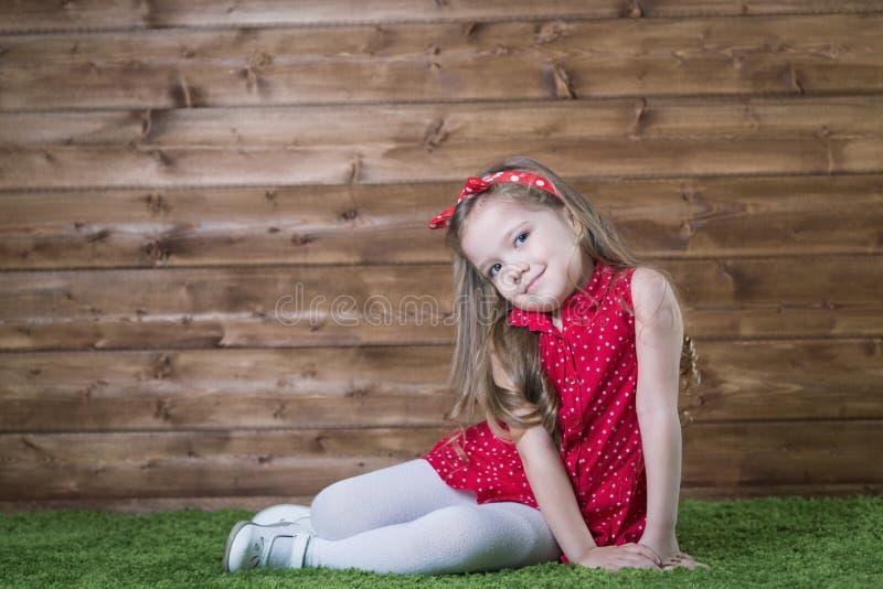 Meisje van vier jaar bij een houten muur royalty-vrije stock afbeelding
