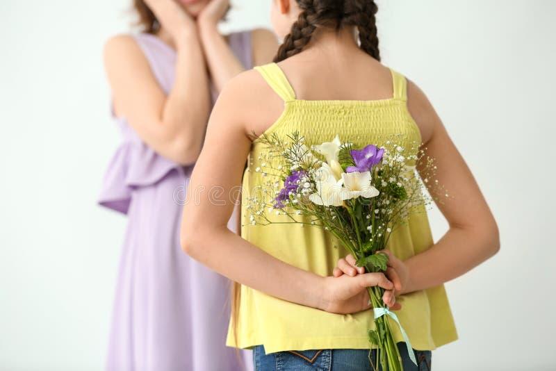 Meisje verbergende bloemen voor moeder achter haar achter, op lichte achtergrond stock fotografie
