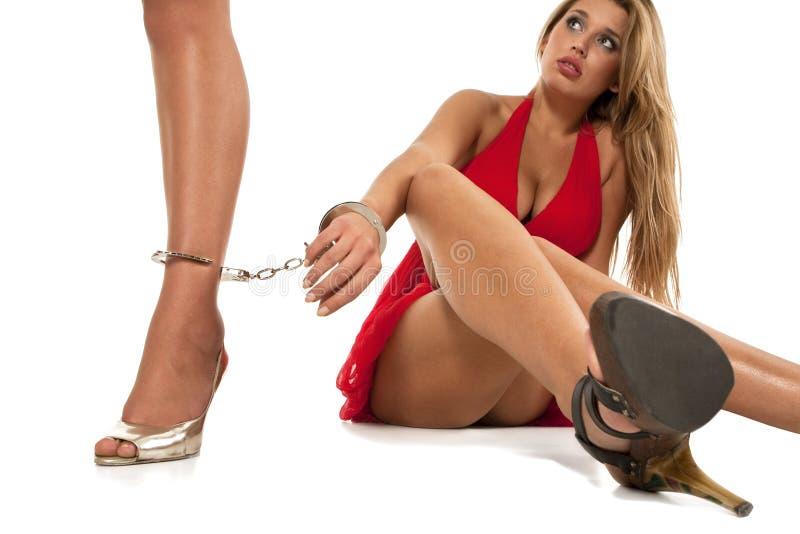 Meisje verbindend met handcuffs aan een andere vrouw stock afbeelding