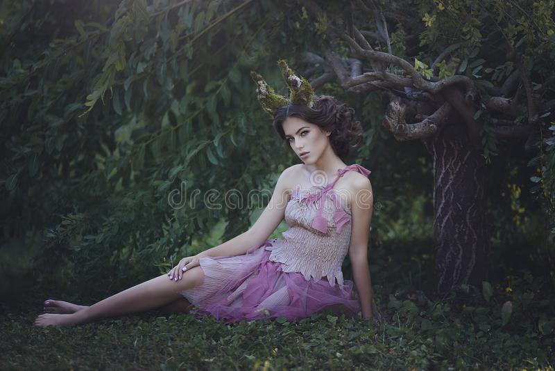 Meisje verrukte Prinses met hoornen die onder een boom zitten Meisjes Mystiek schepsel fawn in sjofele kleren in een feebos royalty-vrije stock fotografie