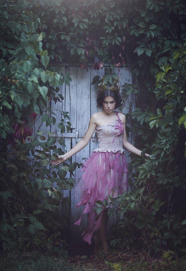 Meisje verrukte Prinses met hoornen Schepsel van de meisjes het Mystieke fee fawn in sjofele kleren dichtbij de oude deur Hallowe stock foto's