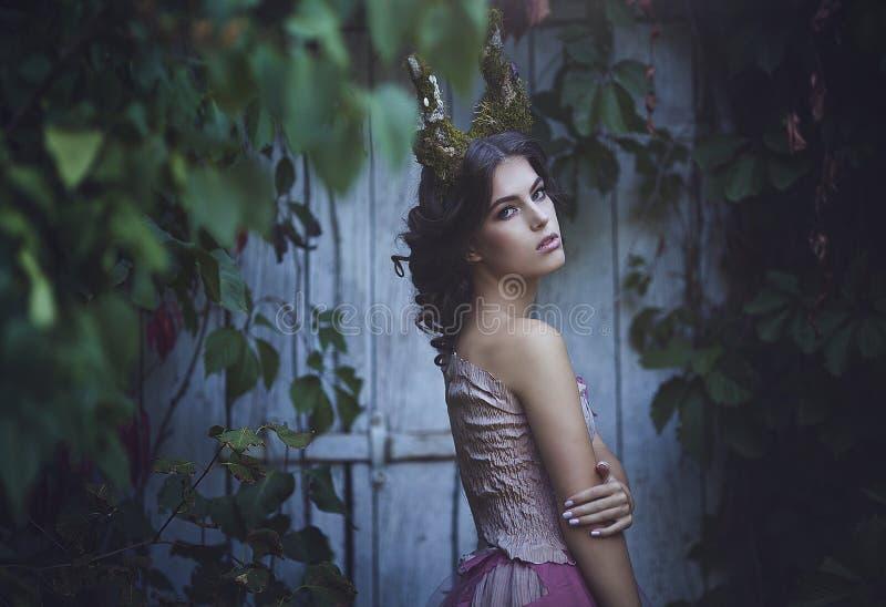 Meisje verrukte Prinses met hoornen Schepsel van de meisjes het Mystieke fee fawn in sjofele kleren dichtbij de oude deur Hallowe stock foto