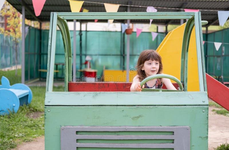 Meisje vijf jaar van pret die de bestuurder van een houten auto op de Speelplaats afbeelden stock fotografie