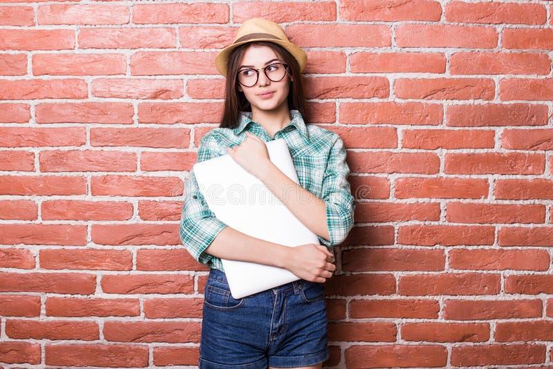 meisje in vrijetijdskleding, hoed en oogglazen die, glimlachend en met dichte laptop in handen stellen stock foto