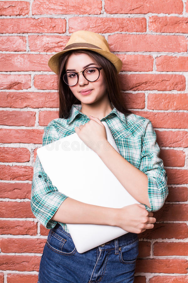 Meisje in vrijetijdskleding, hoed en oogglazen die, glimlachend en met dichte laptop in handen stellen, royalty-vrije stock foto's