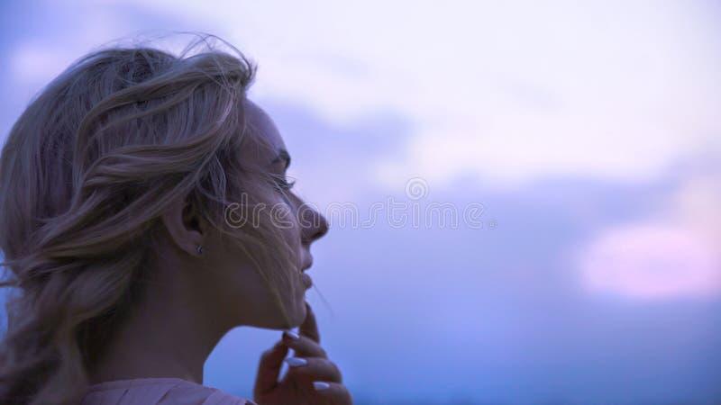 Meisje wat betreft haar lippen, die over de geliefde mens denken die, droevig afstand onderzoeken stock foto