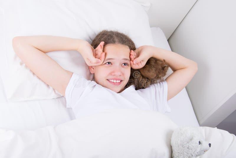 meisje in wit bed, het glimlachen, ontwaken vroeg in de ochtend royalty-vrije stock afbeeldingen