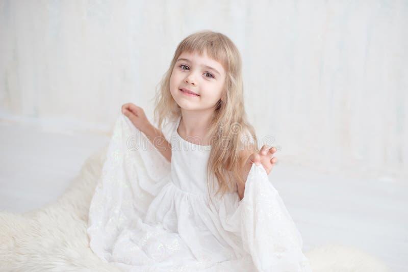 Meisje in witte brede kledingszitting op de vloer royalty-vrije stock fotografie
