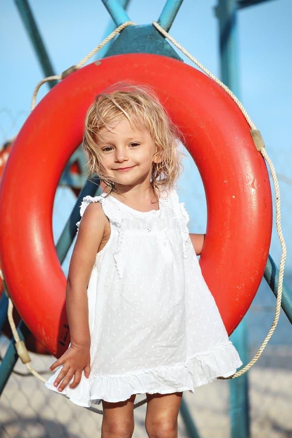 Meisje in witte kleding die en reddingsboei glimlachen houden stock foto's