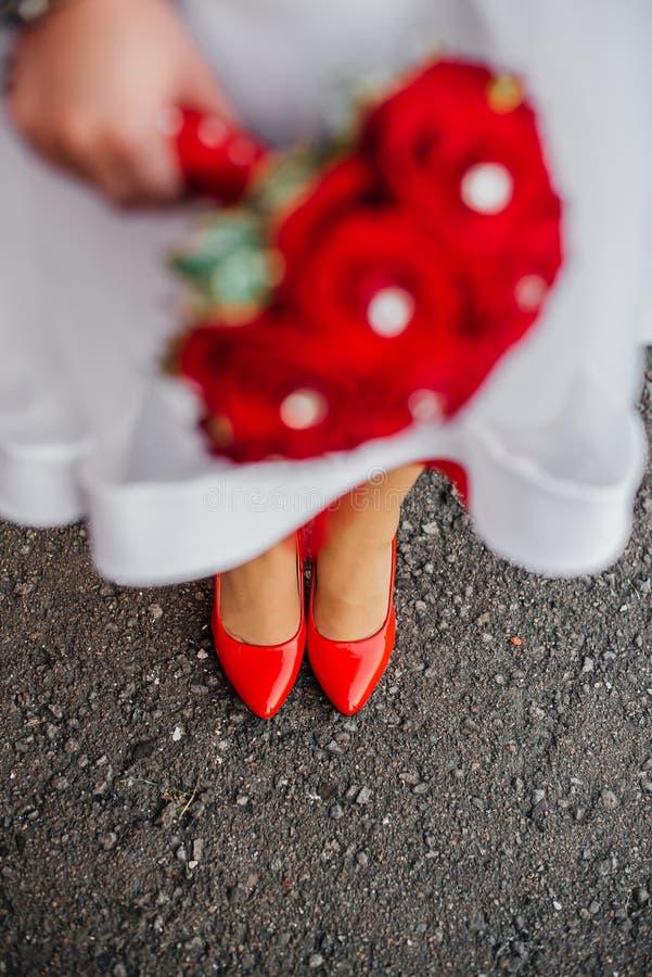Meisje in witte kleding met rood boeket stock afbeeldingen