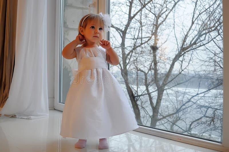 Meisje in witte kleding naast een groot venster royalty-vrije stock foto