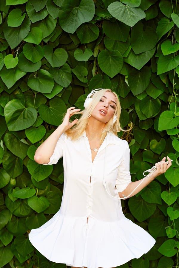 Meisje in witte korte kleding die met hoofdtelefoons dansen stock afbeeldingen