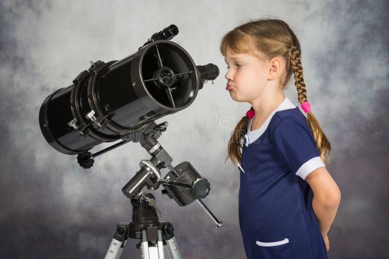 Meisje wordt teleurgesteld door wat hij in de telescoop die zag royalty-vrije stock foto's