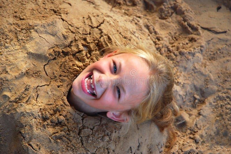 Meisje in zand wordt gegraven dat royalty-vrije stock foto's