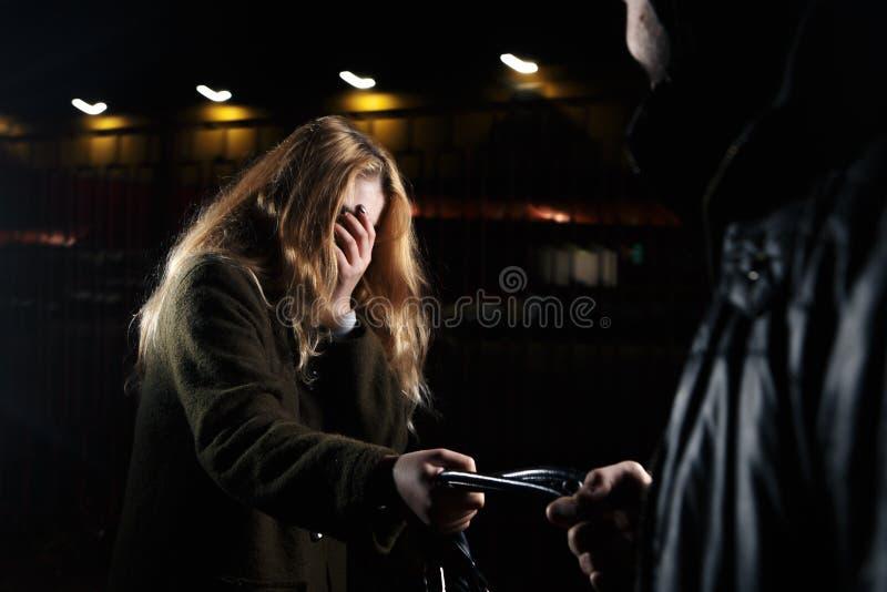 MEISJE ZELF - ziet de DEFENSIEa jonge vrouw een verdachte persoon lopend achter haar en is van plan om tegen een mannetje te verd royalty-vrije stock foto