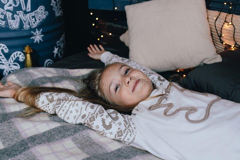 meisje in zich pyjama het uitrekken in bed na kielzog omhoog op de winterochtend royalty-vrije stock fotografie