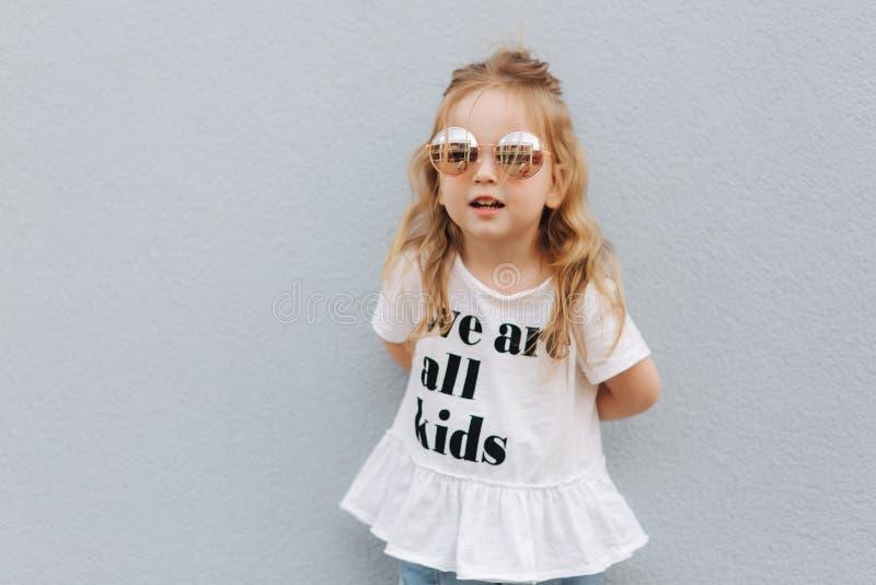 Meisje in zonnebril die aan fotograaf stellen Blonde ountside van het haar vrouwelijke kind royalty-vrije stock foto