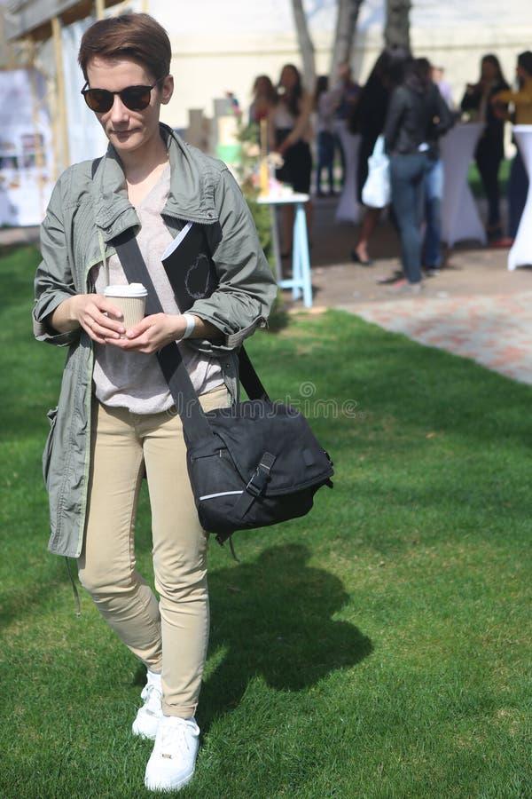 Meisje in zonnebril met koffie na opleiding royalty-vrije stock afbeelding