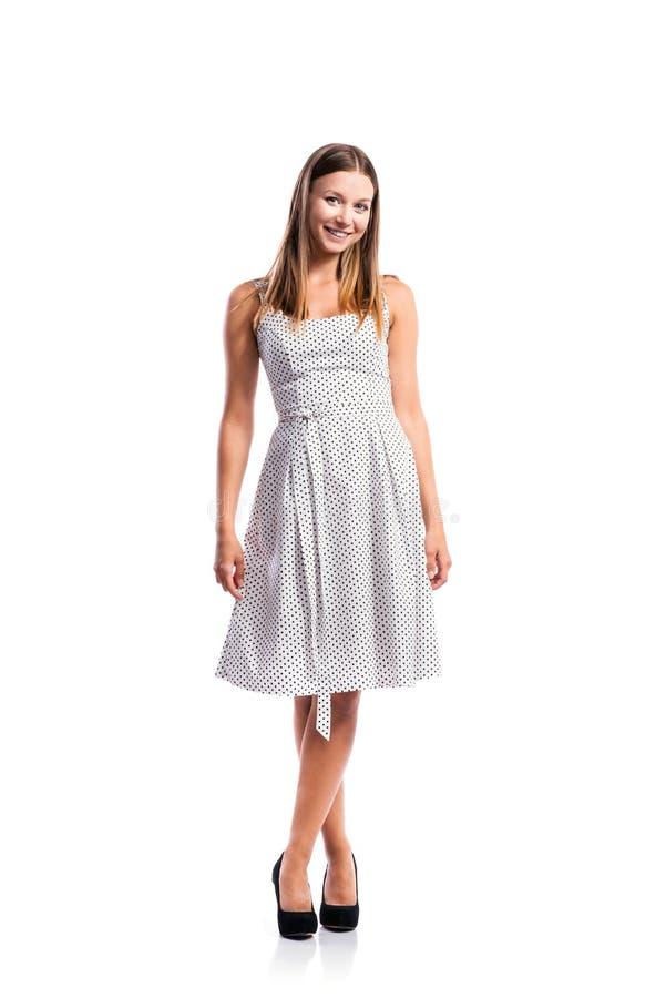 Meisje in zwart-witte gestippelde kleding, hielen, studioschot, isolat stock afbeeldingen