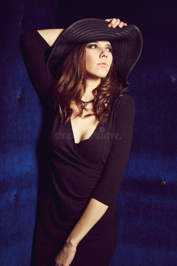 Meisje in zwarte kleding en hoed stock afbeelding