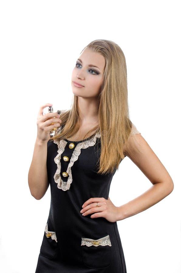 Meisje in zwarte kleding met parfum op witte backgrou stock afbeelding