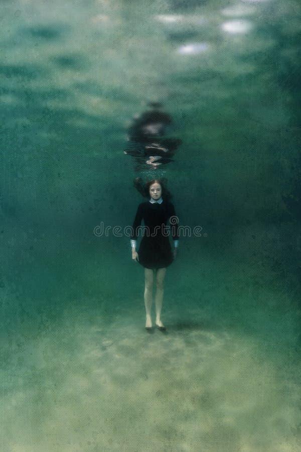 Meisje in zwarte kleding onderwater stock fotografie