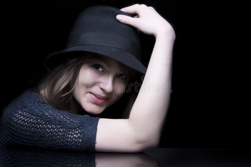 Meisje in zwarte met modieuze zwarte hoed royalty-vrije stock afbeeldingen